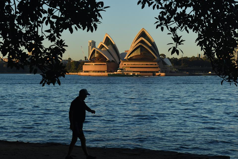 A man walks along the harbour opposite the Sydney Opera House.