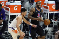 Los Angeles Clippers forward Kawhi Leonard, right, is defended by Phoenix Suns guard Devin Booker during the first half of an NBA basketball game Thursday, April 8, 2021, in Los Angeles. (AP Photo/Marcio Jose Sanchez)