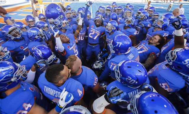 Boise State players,including cornerback Donte Deayon (5), running back Jay Ajayi (27) and tight end Gabe Linehan (87), gather before an NCAA college football game against Air Force in Boise, Idaho, Friday, Sept. 13, 2013. (AP Photo/Otto Kitsinger)