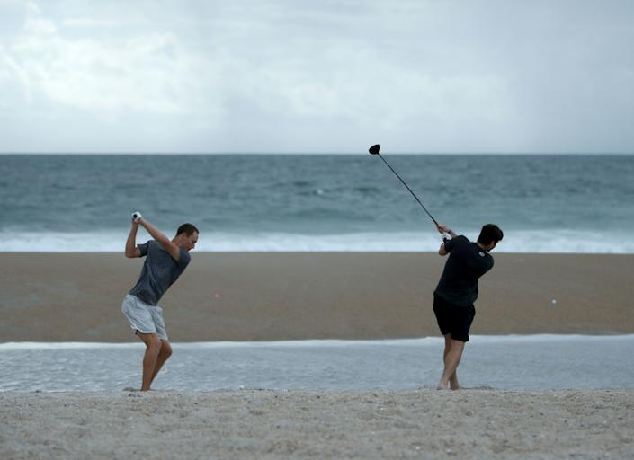 Jacob Whitehead (L) and Matt Jones hit golf balls into the surf in Wrightsville Beach on Sept. 11 as Hurricane Florence approaches.