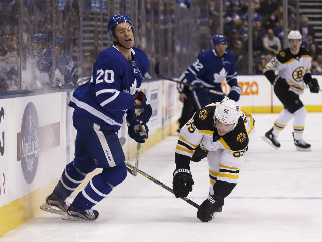 Toronto Maple Leafs center Dominic Moore (20) and Boston Bruins center Noel Acciari (55) collide during the first period of an NHL hockey game Saturday, Feb. 24, 2018, in Toronto. (Cole Burston/The Canadian Press via AP)