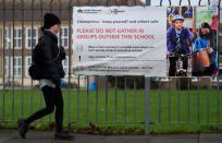 A woman walks past a social distancing health message outside of a secondary school in London