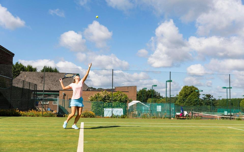 Woman serving during a tennis match on grass court - GETTY IMAGES