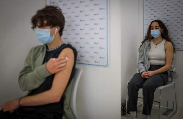 Hisham Arafat, 15, left, and his sister Maria Arafat, 17, receive their COVID-19 vaccine in Calgary last May. Currently, 75.2 per cent of eligible Albertans are fully vaccinated with two vaccine doses. (Leah Hennel/AHS - image credit)