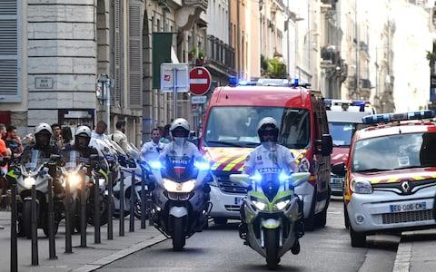 French police escort the emergency services following a suspected package bomb blast along a pedestrian street in the heart of Lyon, southeast France - Credit: PHILIPPE DESMAZES/AFP