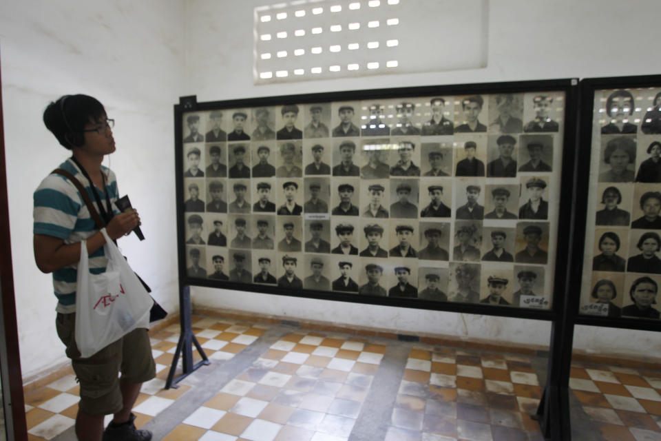 A tourist views portraits of victims executed by the Khmer Rouge regime at the Tuol Sleng Genocide Museum in Phnom Penh, Cambodia on Feb. 5, 2018. Cambodians on Monday, April 12, 2021, continued to condemn an Irish photo restorer for altering photographs of victims of their country's 1970s genocide to show them smiling, saying his decision and that of an international media group to publish them showed horrible judgement.(AP Photo/Heng Sinith)