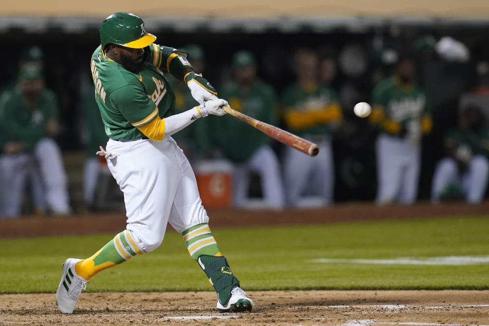 Oakland Athletics' Josh Harrison hits a two-run single against the San Francisco Giants during the fourth inning of a baseball game in Oakland, Calif., Friday, Aug. 20, 2021. (AP Photo/Jeff Chiu)