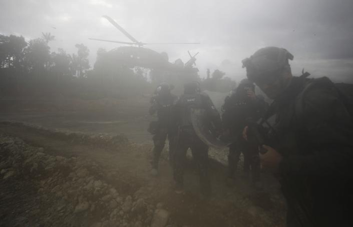 """A helicopter arrives to extract National Police from an illegal gold mining operation where they destroyed machinery as part of the Armed Forces' """"Operation Guamuez III"""" in Magui Payan, Colombia, Tuesday, April 20, 2021. Illegal gold mining is common in Colombia, especially wildcat mines in poverty-stricken areas dominated by criminal gangs with little state presence. (AP Photo/Fernando Vergara)"""