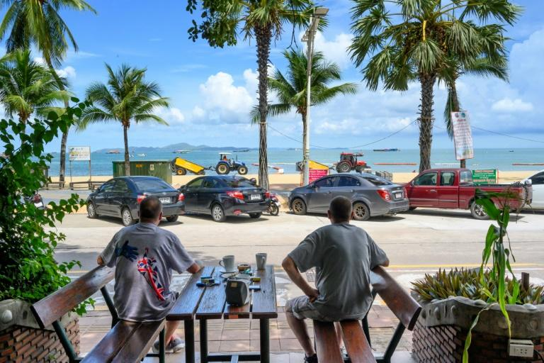 Two beachgoers enjoy a coffee in Pattaya after lockdown restrictions were lifted (AFP Photo/Mladen ANTONOV)