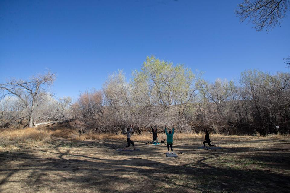 Community members of Hillsboro, N.M., partake in morning yoga at the Black Range Museum Public Park. Area residents got their COVID-19 vaccination the same day thanks to a mobile vaccination unit sent by the New Mexico Department of Health.