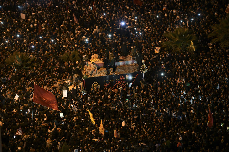 Mourners surround a truck carrying the flag draped coffins of Gen. Qassem Soleimani and his comrades in the holy city of Qom south of the capital Tehran, Iran, Monday, Jan. 6, 2020. The men were killed in a U.S. drone strike on Friday, Jan. 3 in Iraq. The funeral drew a crowd said by police to be in the millions in the Iranian capital, filling thoroughfares and side streets as far as the eye could see. (Amir Hesaminejad/Tasnim News Agency via AP)