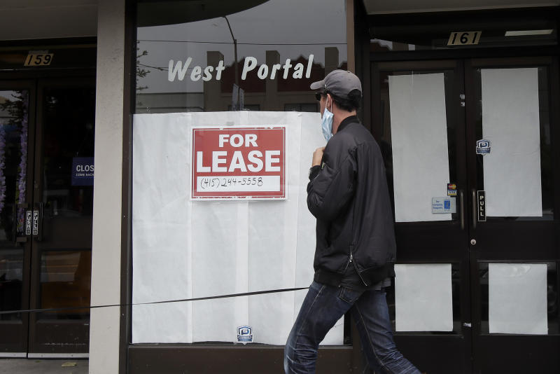 A man wearing a mask walks past a For Lease sign posted on the window of a storefront during the coronavirus outbreak in San Francisco, Sunday, June 21, 2020. (AP Photo/Jeff Chiu)