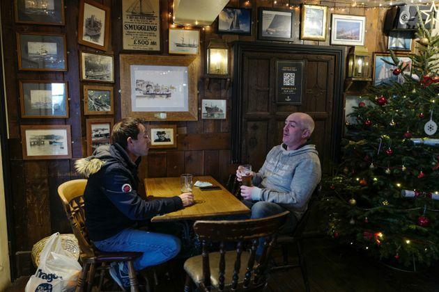 Customers enjoy their drinks next to a Christmas tree at the Chainlocker pub on December 2, 2020 in Falmouth, United Kingdom