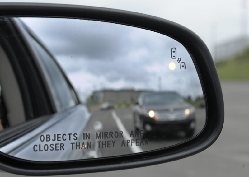 In this photo taken Tuesday, May 22, 2012, professional test driver J.D. Ellis of Cincinnati, Ohio, demonstrates the side mirror warning signal in a Ford Taurus at an automobile testing area in Oxon Hill, Md. The display at a recent transportation conference was a peek into the future of automotive safety: cars that to talk to each other and warn drivers of impending collisions. Later this summer, the government is launching a yearlong, real-world test involving nearly 3,000 cars, trucks and buses using volunteer drivers in Ann Arbor, Mich. (AP Photo/Susan Walsh)