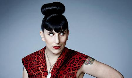 Woman with upper arm tattoo, bright red lipstick, and badass bangs