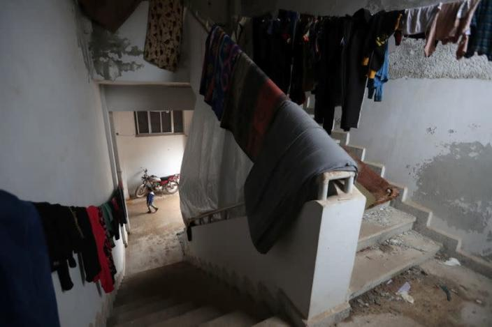 Laundry for Internally displaced people hangs inside an empty school and university compound used as shelter, in Azaz