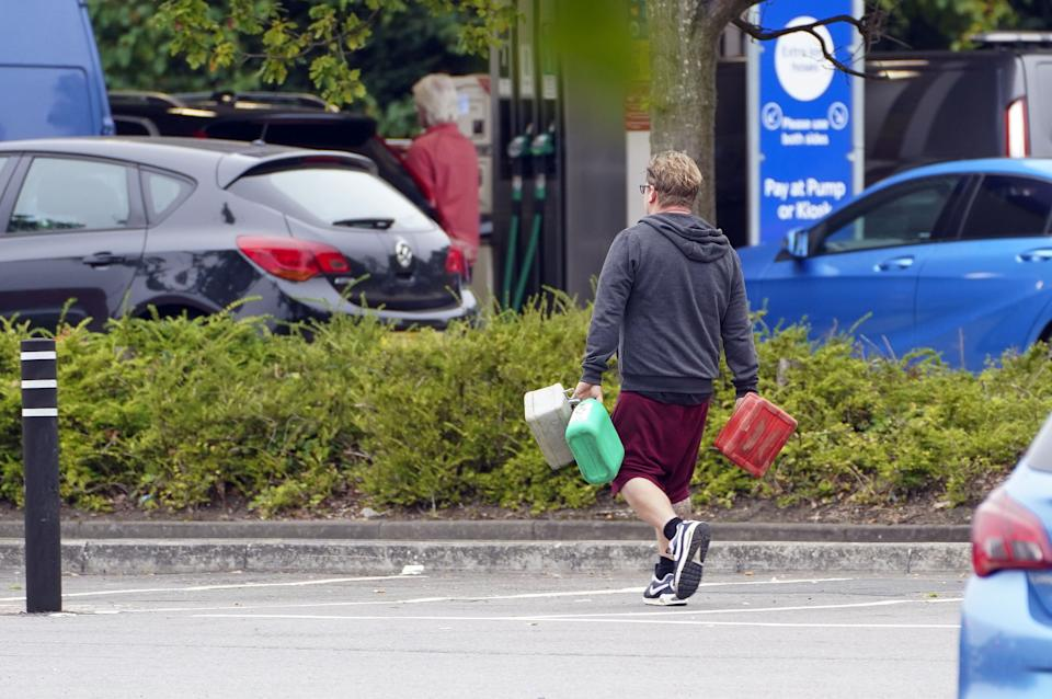 A man carrying containers at a Tesco Petrol Station in Bracknell, Berkshire. Picture date: Saturday September 25, 2021. (Photo by Steve Parsons/PA Images via Getty Images)