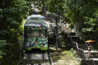 A Peak Tram passes uphill of the Victoria Peak in Hong Kong on June 16, 2021. Hong Kong's Peak Tram is a fixture in the memories of many residents and tourists, ferrying passengers up Victoria Peak for a bird's eye view of the city's many skyscrapers. (AP Photo/Vincent Yu)