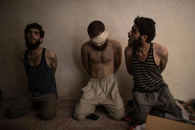 <p>Two men are detained along with a suspected Islamic State fighter, center, to be questioned in a basement as Iraqi forces continue their advance against Islamic State militants in the Old City of Mosul, Iraq, Monday, July 3, 2017. The two men were released. (Photo: Felipe Dana/AP) </p>