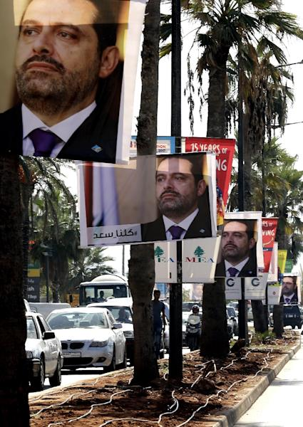 """Photographs of resigned Lebanese Prime Minister Saad Hariri line Beirut's seaside corniche on November 10, 2017, with a caption in Arabic reading: """"#We_are_all_Saad"""" (AFP Photo/JOSEPH EID)"""