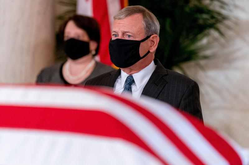 John Roberts and Elena Kagan wear face masks behind the flag-draped casket of Ruth Bader Ginsburg