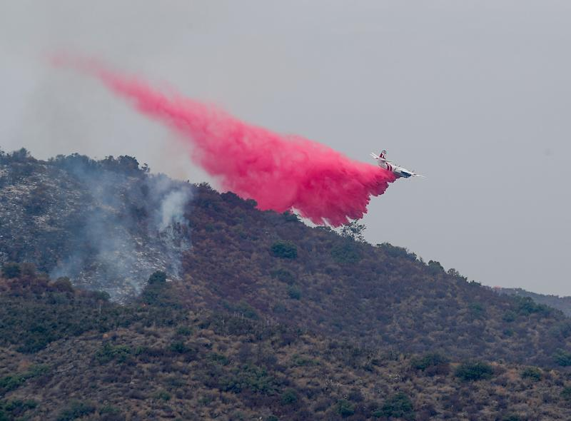 A Cal Fire aircraft drops fire retardant on the Tenaja fire in the Murrieta foothills near Vineyard Parkway, September 5, 2019.
