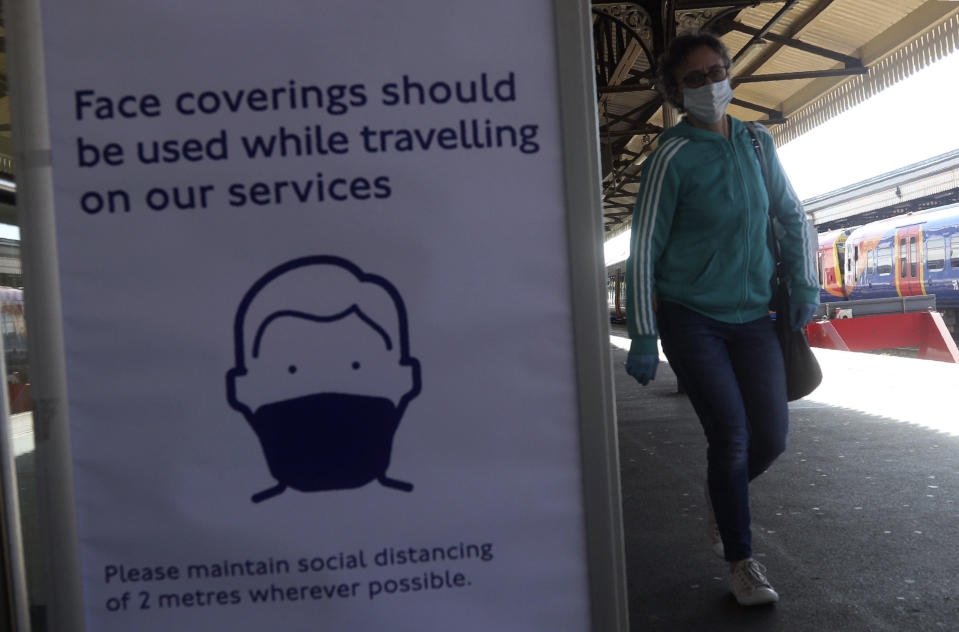 A sign advising passengers to wear a face mask at Clapham Junction station as train services increased as part of the easing of coronavirus lockdown restrictions, in London, Monday May 18, 2020.Britain's Prime Minister Boris Johnson announced last Sunday that people could return to work if they could not work from home. (Yui Mok/PA via AP)