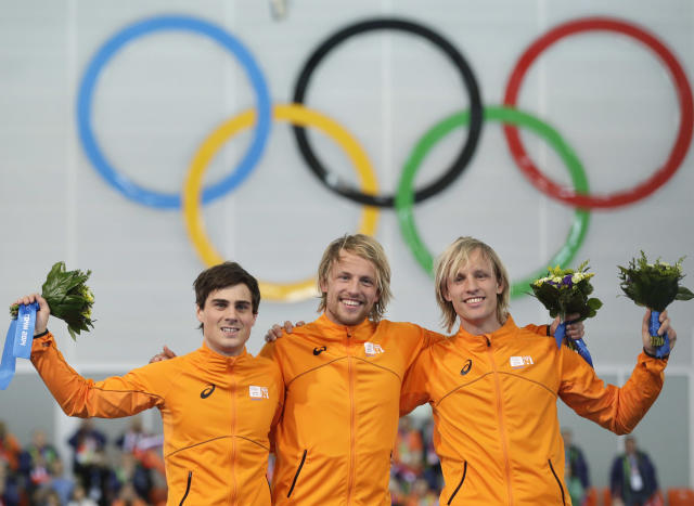 Athletes from the Netherlands, from left to right, Silver medallist Jan Smeekens, gold medallist Michel Mulder and bronze medallist Ronald Mulder stand on the podium during the flower ceremony for the men's 500-meter speedskating race at the Adler Arena Skating Center at the 2014 Winter Olympics, Monday, Feb. 10, 2014, in Sochi, Russia. (AP Photo/Patrick Semansky)