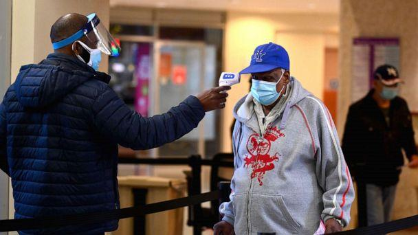 PHOTO: A staff member checks the temperature of a visitor at Woodhull Medical and Mental Health Center, Dec. 1, 2020, in New York. (Angela Weiss/AFP via Getty Images)