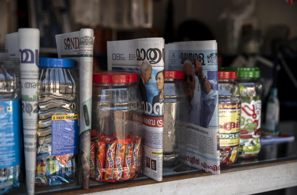 Malayalam language newspapers that have as the main front page news, President-elect Joe Biden's win in the U.S. presidential election are displayed for sale between bottles of candies at a roadside shop in Kochi, Kerala state, India, Sunday, Nov.8, 2020. (AP Photo/R S Iyer)