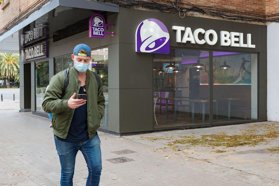 A man wearing a face mask walks past a fast food restaurant Taco Bell. (Photo by Xisco Navarro/SOPA Images/LightRocket via Getty Images)