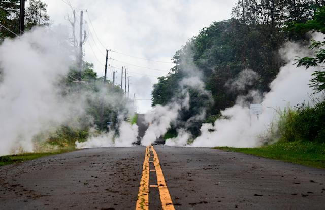 <p>Steam rises from a fissure on a road in Leilani Estates subdivision on Hawaii's Big Island on May 4, 2018. Up to 10,000 people have been asked to leave their homes on Hawaii's Big Island following the eruption of the Kilauea volcano that came after a series of recent earthquakes. (Photo: Frederic J. Brown/AFP/Getty Images) </p>