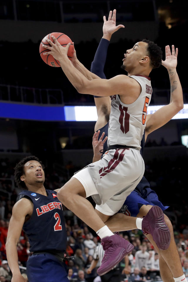 Virginia Tech guard Justin Robinson drives to the basket past Liberty guards Darius McGhee (2) and Elijah Cuffee during the second half of a second-round game in the NCAA men's college basketball tournament Sunday, March 24, 2019, in San Jose, Calif. (AP Photo/Jeff Chiu)