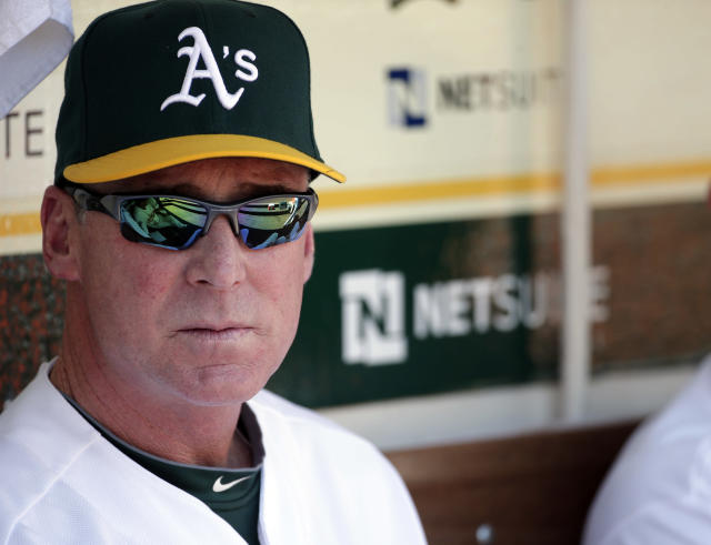 Oakland Athletics manager Bob Melvin watches from the dugout as his team warms up before a baseball game against the Seattle Mariners on Monday, Sept. 1, 2014, in Oakland, Calif. (AP Photo/Marcio Jose Sanchez)