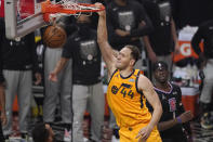 Utah Jazz forward Bojan Bogdanovic, left, dunks as Los Angeles Clippers guard Reggie Jackson watches during the first half in Game 4 of a second-round NBA basketball playoff series Monday, June 14, 2021, in Los Angeles. (AP Photo/Mark J. Terrill)