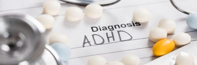 Glasses, pills and a stethoscope with an ADHD diagnosis