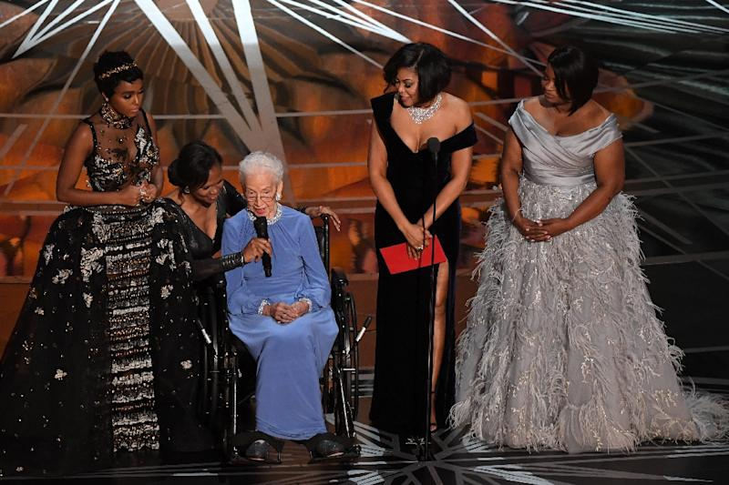 NASA physicist Katherine Johnson (C) is surrounded by singer and actress Janelle Monae (L), actress Taraji P. Henson (2ndR) and actress Octavia Spencer (R) as they present on stage the Best Documentary Feature award at the 89th Oscars (AFP Photo/Mark RALSTON)