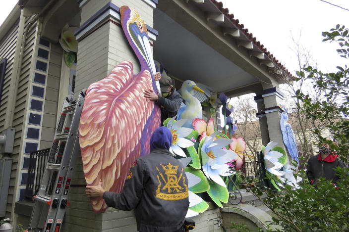 Parade float workers Travis Keene, left, and Joey Mercer position a pelican while fellow crew member Chelsea Kamm, right, looks on while decorating a house in New Orleans on Friday, Jan. 8, 2021. All around the city, thousands of houses are being decorated as floats because the coronavirus pandemic has canceled parades that usually take place on Mardi Gras. (AP Photo/Janet McConnaughey)