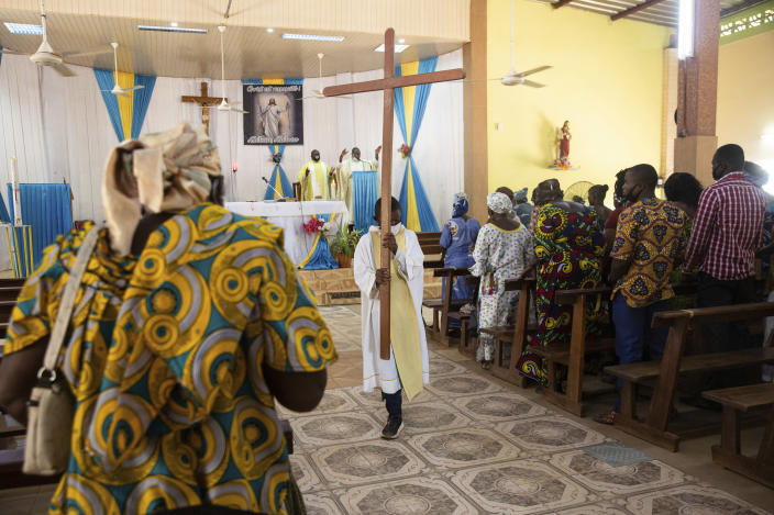 An altar boy carries a cross as Noel Henri Zongo, priest at the Church of the Sangoulé Lamizana military camp in Ouagadougou, Burkina Faso, celebrates Mass on Sunday, April 11, 2021. Just seven chaplains, hailing from Protestant, Catholic and Muslim faiths, are charged with spiritually advising some 11,000 soldiers and helping maintain their morale. (AP Photo/Sophie Garcia)