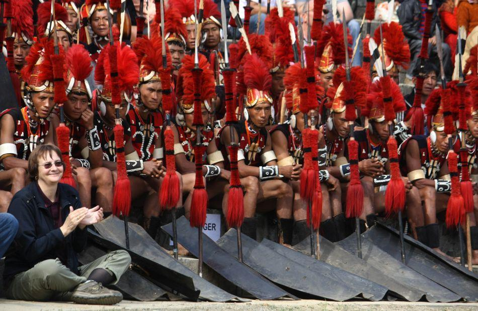 A foreign tourist cheers Naga performers. During the annual Hornbill Festival, visitors flock to Nagaland. Indian residents require an Inner Line Permit to enter while foreign nationals, with the exception of visitors from Pakistan and China, must register at the nearest Foreigners Registration Office (FRO).