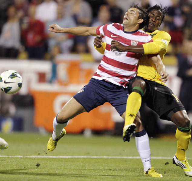 United States' Herculez Gomez, left, and Jamaica's Lovel Palmer fight for a loose ball during the first half of a World Cup qualifying soccer match, Tuesday, Sept. 11, 2012, in Columbus, Ohio. (AP Photo/Jay LaPrete)