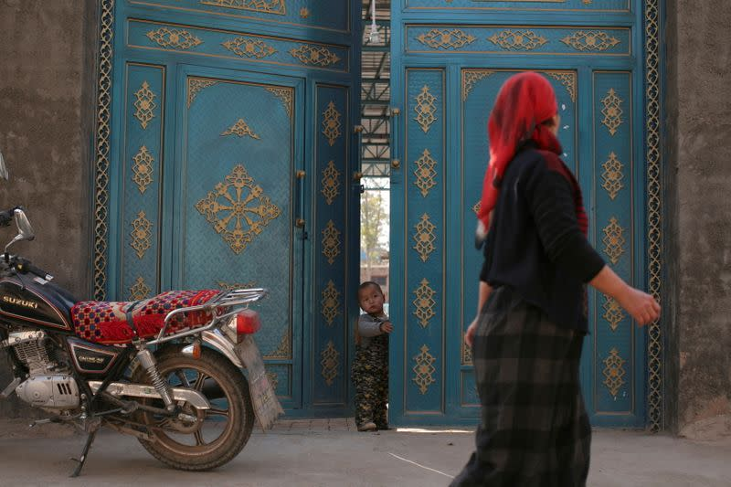 FILE PHOTO: A child looks out from a door as a Uighur woman walks by in a residential area in Turpan, Xinjiang Uighur Autonomous Region