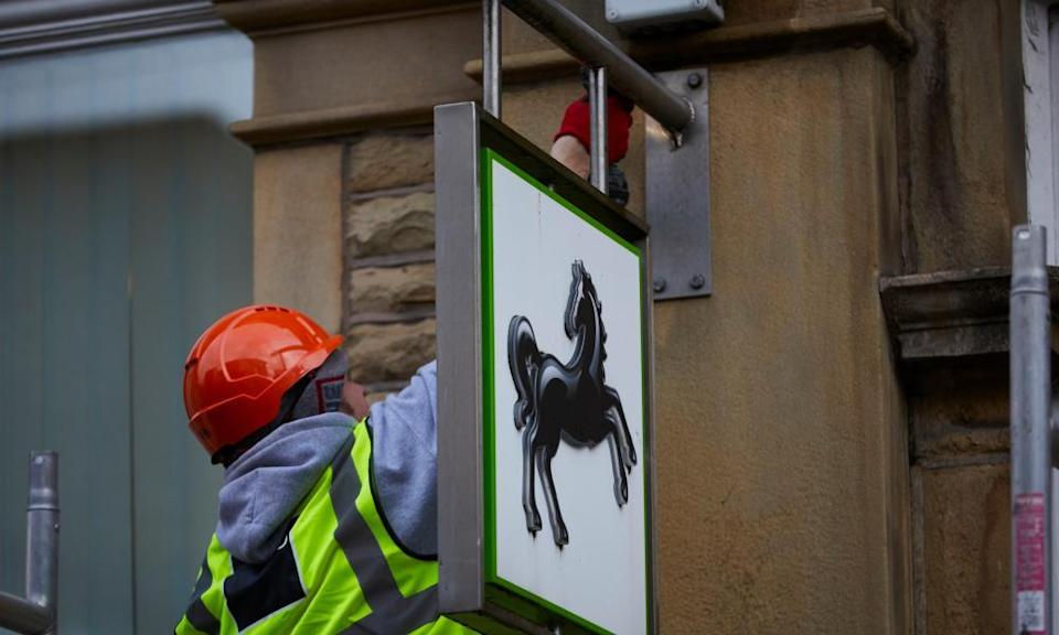A workman on a ladder unbolting a Lloyds sign from the side of a building