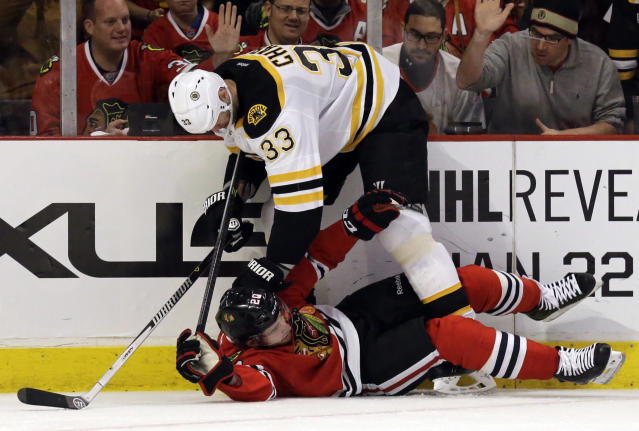Chicago Blackhawks' Brandon Saad (20), bottom, is checked by Boston Bruins' Zdeno Chara (33) during the second period of an NHL hockey game in Chicago, Sunday, Jan. 19, 2014. (AP Photo/Nam Y. Huh)