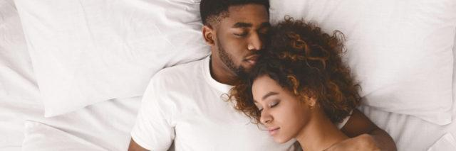 Young black couple sleeping together in bed