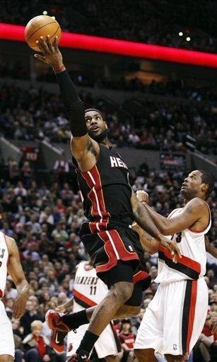 Miami Heat's LeBron James, left, shoots a layup past Portland Trail Blazers' Marcus Camby (23) during the first quarter of an NBA basketball game, Thursday, March 1, 2012, in Portland, Ore. (AP Photo/Rick Bowmer)