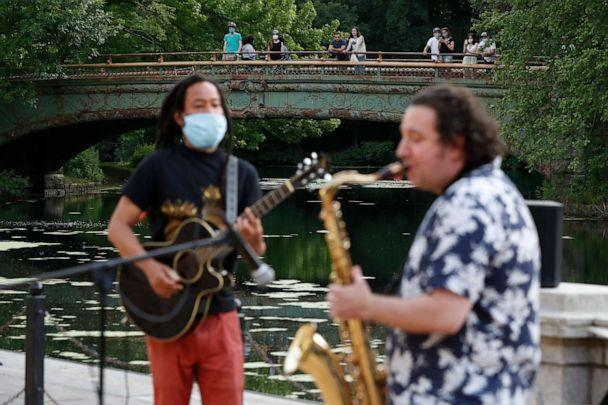 PHOTO: People watch from the Lullwater Bridge in Brooklyn's Prospect Park in New York as Alegba Jahyile, left, and Mark Kraszewski play as part of Alegba and Friends' free nightly outdoor concerts in New York City, June 18, 2020. (Kathy Willens/AP)