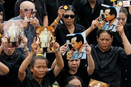 Mourners gather outside of the Grand Palace to sing for a recording of the royal anthem in honour of Thailand's late King Bhumibol Adulyadej, in Bangkok