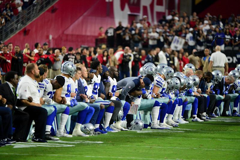The Dallas Cowboys players, coaches and staff take a knee prior to standing for the National Anthem during a game against the Arizona Cardinals at University of Phoenix Stadium.