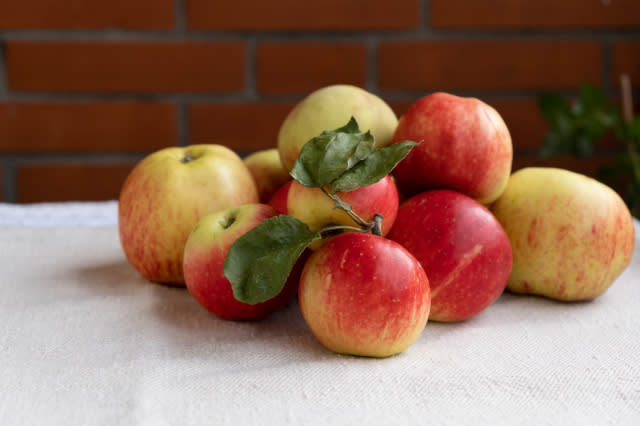 the summer harvest, ripe and juicy apples, lies on the table covered with a linen tablecloth